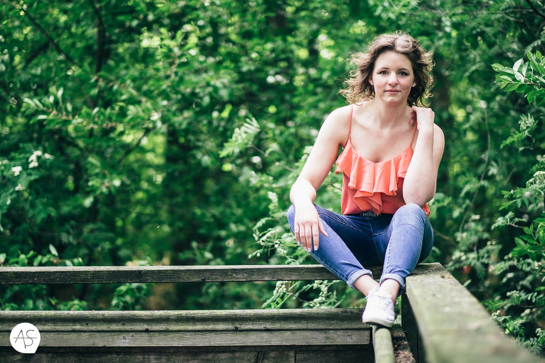 Portrait sitzend auf einem Geländer im Wald