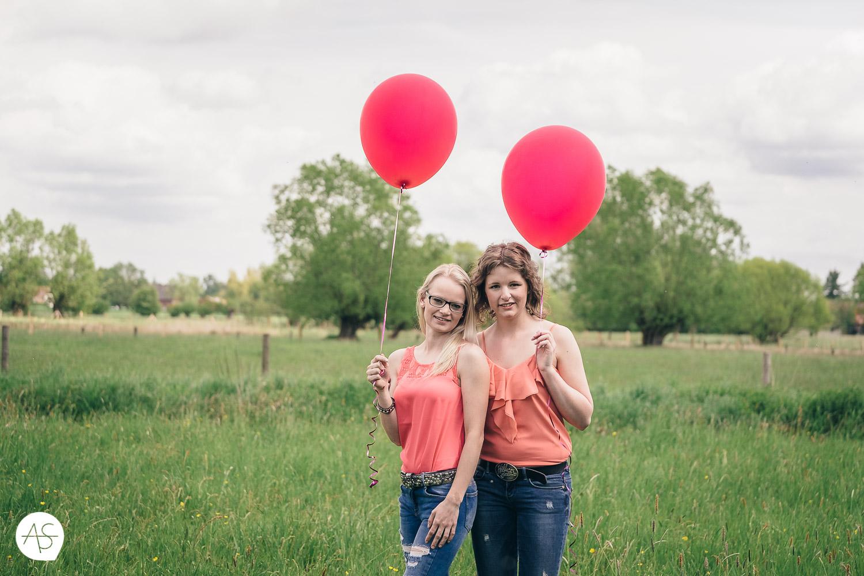 Freundinnen auf einer Wiese mit roten Ballons