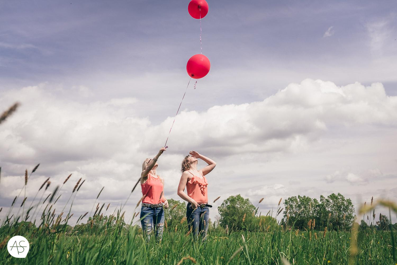 Freundinnen auf einer Wiese lassen  roten Ballons fliegen